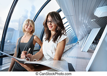 Businesswomen in futuristic interior - Two businesswomen...
