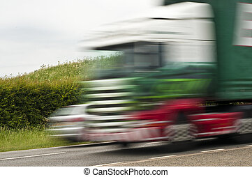 Lorry and car speeding on road