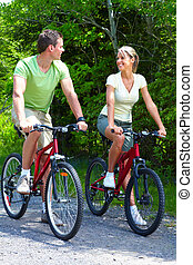 Riding couple. - Young smiling couple  riding  in the park
