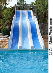 swimming pool with slides on holiday in tropical environment