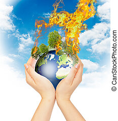 Womanish hands holding burning Earth.