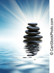 Stack of zen stones reflects in blue water surface