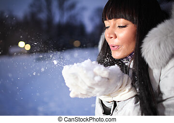 Beautiful woman in winter park, blowing snow playfully