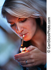 Woman smoking - Beautiful woman lighting cigarette Close-up,...