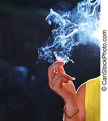 Cigarette smoke - Female hand with smoking cigarette...
