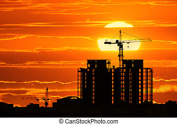 Construction project silhouette against sunset sky with big...