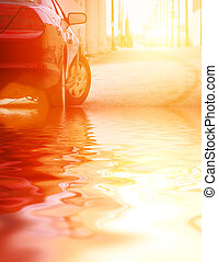 Car in water, closeup - Red car reflects in water on sunny...