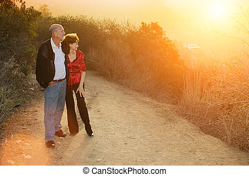 Happy mature couple - Mature couple enjoying sunset on a...