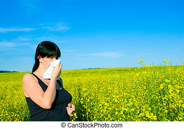 Allergy Young woman blowing her nose on the rapeseed field