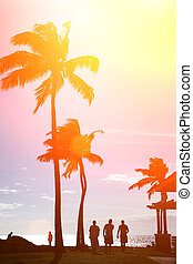Tropical beach at sunset - Surfers silhouettes walking under...