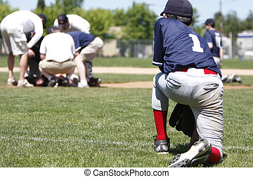 Baseball player kneeling while injured player is checked...