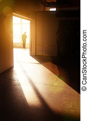 Man in building - Male silhouette in empty interior looking...