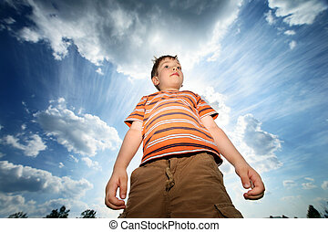 Boy outdoors - Boy standing over blue cloudy sky Powerful...