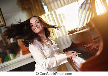 Pianist - Happy young woman playing piano indoors Closeup,...