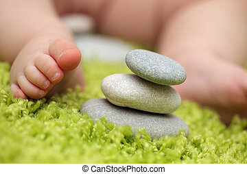 Baby feet next to stack of zen stones. Closeup, shallow DOF.