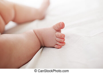 Baby foot - Six month old baby feet with cute toes on white...