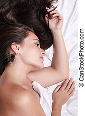 Woman in bed - Portrait of beautiful woman lying on white...