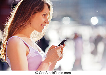 Beautiful young woman with mobile cell phone in city...