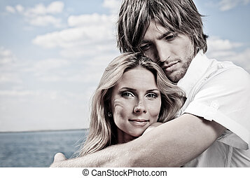 feel - Beautiful young couple posing together over the sea.