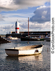 Small Boat tied in a harbour with Lighthouse and Cloudy sky...