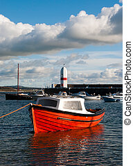Small Fishing Boat tied in a harbour with Lighthouse