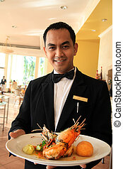 waiter holding food at restaurant - asian waiter smiling and...