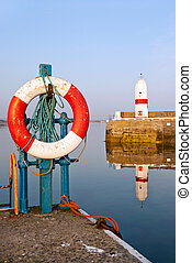 White and Red Life Buoy in Harbour with Lighthouse