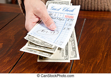 Woman paying bill - A woman pays her meal bill with cash.