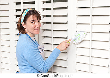 Woman dusting window shutters - A homemaker uses a hand held...