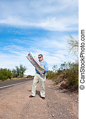 Man on deserted road reading map - A man stands along a...