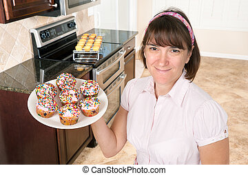 Homemaker holding plate of cupcakes - A homemaker shows off...