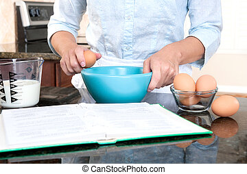 Woman cooking - A homemaker cracks an egg into a mixing bowl...