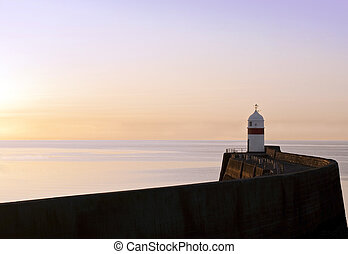 Lighthouse at the end of a breakwater wall during sunrise