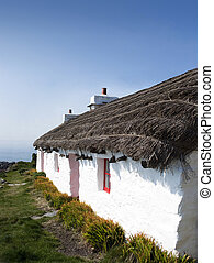 Old traditional white cottage with thatched roof and red...