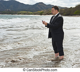 Keeping in Touch - Businessman standing barefoot on a beach...