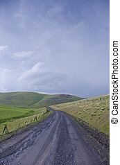 Gravel rural road beneath stormy sky - Black gravel road...