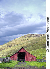 Red barn in dry hill western landscape