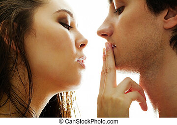 Amorous couple - Pretty brunette touching male lips by her...