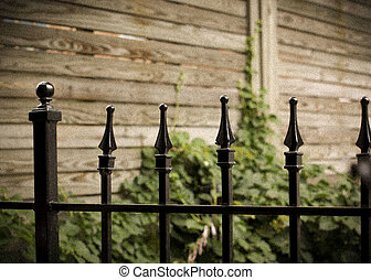 Iron fence vingette - Iron fence against wood fence in the...
