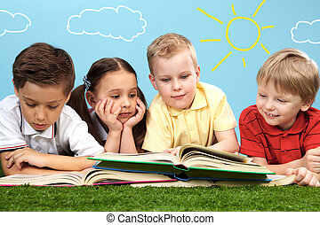 Friends reading - Group of happy children lying on a green...