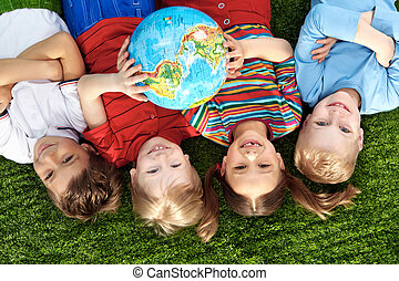 Peace on Earth - Group of happy children lying on a green...
