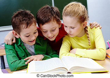 Reading book - Portrait of two guys and girl reading book in...