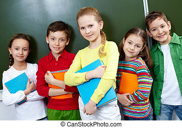 Classmates - Portrait of five pupils looking at camera in...