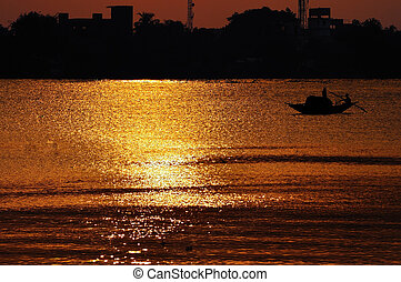 Sunset, Country boat heading towards golden rays, river...