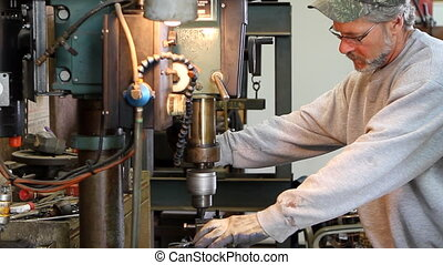Mechanic Operating Drill Press - Mechanic operates a drill...