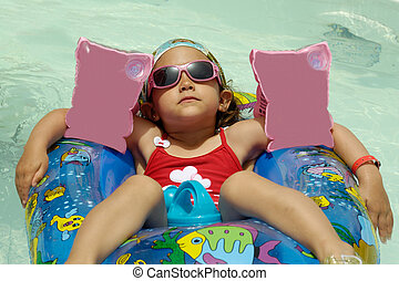 Child in pool relaxing - Young child is relaxing in pool