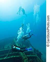 Ascent from a wreck - Divers ascending from a wreck to the...