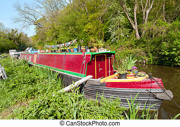 Narrowboat home - A bright red narrowboat home, moored on...