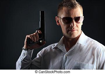 gun - Portrait of a handsome man holding a gun. Studio shot.