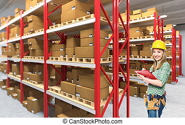 woman in warehouse - smiling manual worker in classic...